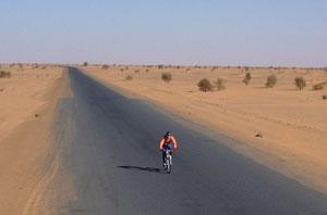 A lone cyclist in the Sahara desert.