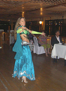 A belly dancer entertains the passengers.