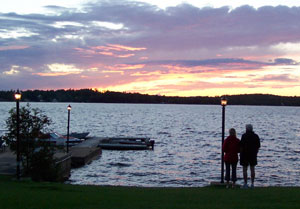 A couple takes in the sunset over Lac Nominingue.