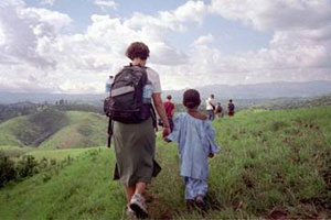 A volunteer walks with a child in Cameroon.