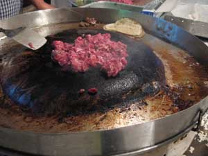 Inverted wok-like contraption for cooking meat at a mobile taco stand