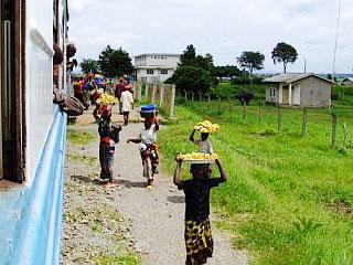 Women selling bananas and chapattis run alongside the Tazara train.