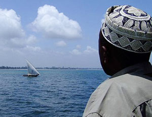 Man watching a dhow from the ferry from Dar es Salaam to Zanzibar