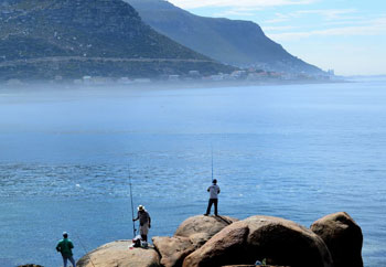 Fishermen hope to get lucky from rocks beside Fishhoek Beach.