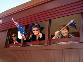 Patriotic Aussies wave from the windows of the Pichi Richi, the old troop train
