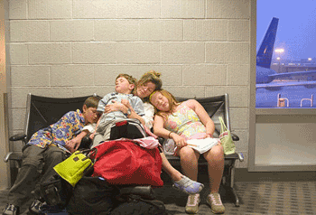 A family uncomfortably rests while waiting for their flight.