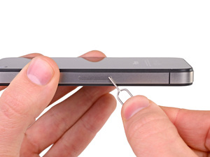 Prying open an iPhone4S to change the SIM card, which is a good idea for overseas use.
