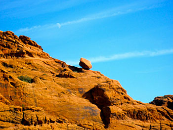 A boulder balances on the edge of a mountain as the daytime moon illuminates the sky.