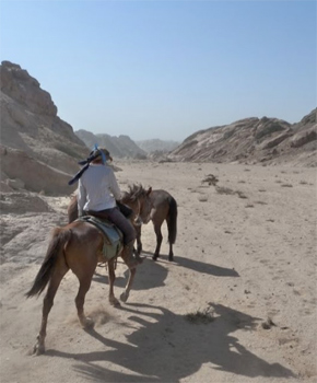 Riding through a dry riverbed.