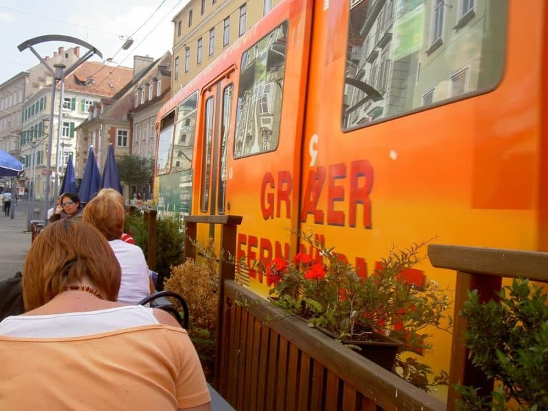 The tram is right next to the sidewalk in downtown Graz.