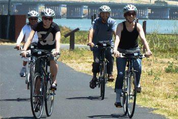 Bikers enjoy a beatiful ride through the urban beach town of Oakland, California
