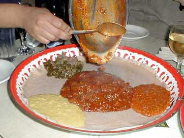 Adding goat or mutton to injera in Ethiopia.