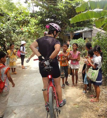 A cyclist greeted warmly by young Cambodian children.