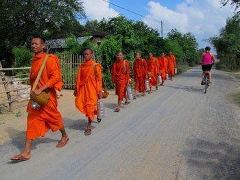 Orange-robed monks are a common roadside site in Cambodia.