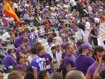 Soccer fans decked out in the Florence team's purple color in the stands