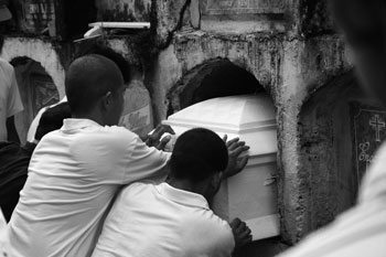 Mourners bury a coffin in Capiz Province, Philippines. The deceased is the grandmother of two boys I worked with; I was invited to stay up all night for the wake and eat dried fish, drink native coconut wine (tuba) and play Bingo.