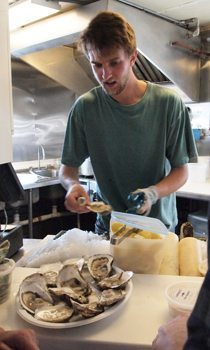 Shucking oysters at Larsen's Fish, Menemsha.