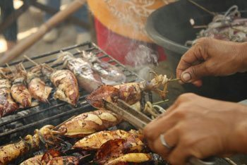 Locals in Zarraga grill squid (pusit). Iloilo Province is known for its fresh seafood.