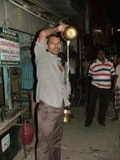 A vendor prepares warm milk for sale in India.
