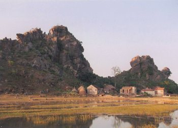 A typical scene outside Van Long Nature Preserve, not far from Cuc Phuong. The landscape is dominated by the huge, weirdly shaped, eroded limestone hills. Like many homes in the area, the house in the foreground has a fish pond in its front yard. Photo by Dan Drollette