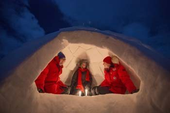 Friends huddle around a candle in an igloo they built that afternoon. Courtesy photo.