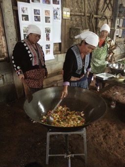 Hmong women preparing a big stir fry for lunch.