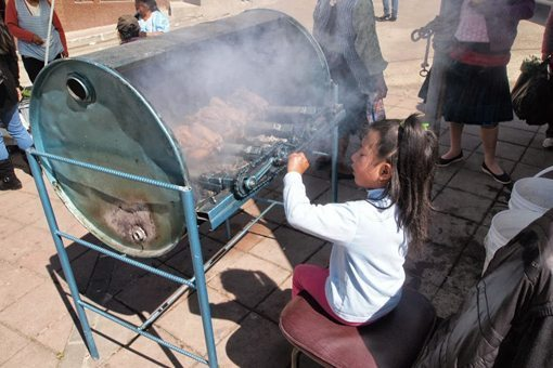 This little girl has the hardest job, turning the chicken rotisserie.