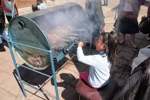 This little girl has the hardest job, turning the chicken rotisserie.