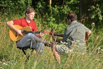 Guitarist in field near River Isar