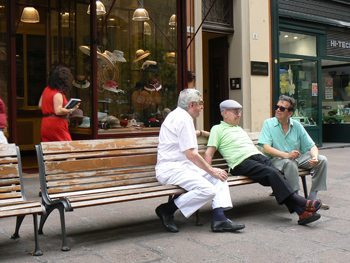 All over Bologna there are men who hang out chatting on benches. photo by Max Hartshorne.