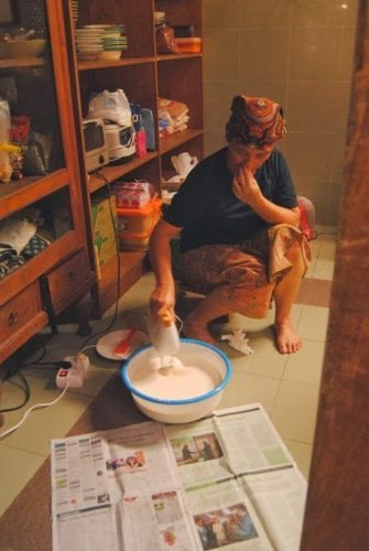 Ibu Dar preparing handmade butter in her rustic kitchen