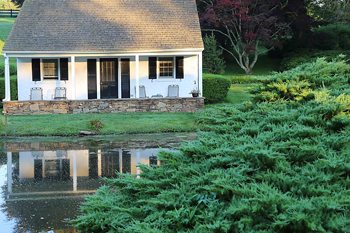 The Inn at Whitewing Farm - Our lovely cottage reflected in the pond.