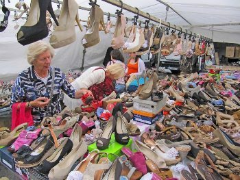 Women and many shoes at the market.