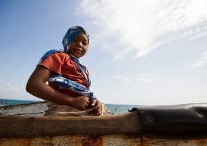 A girls on Isle de Mozambique waits for her fisherman father to return.