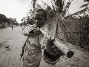 A local boy imitates the rebels and other forces that play important roles in Mozambique.