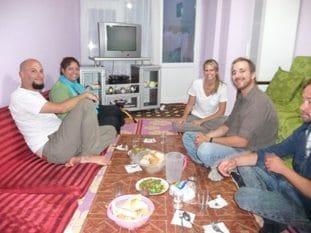 Tour group enjoying dinner with Delhi family through Urban Adventures