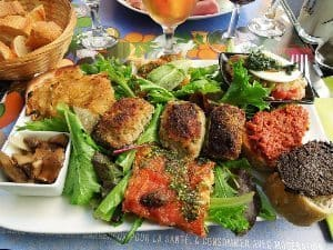 Assiette Provençal (Clockwise from Top Left: Pissaladière, Salade Niçoise, Pâté à Tartiner over bread, Pizza, and Marinated Mushrooms. Center: Farcis Niçois). photos by Derek Noll.