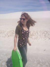 Steffi sledding in the white sand dunes