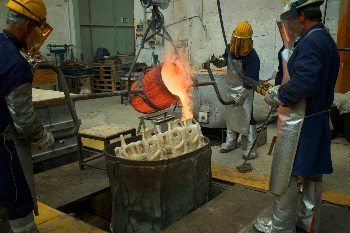 A precision team of foundry workers pour molten bronze into a form that is part of a large Botero sculpture. Photos by John Keahey