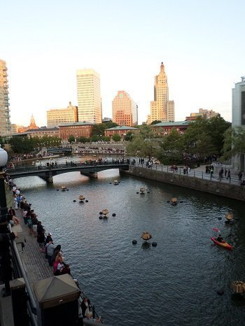 Preparing for the WaterFire Festival lighting at sunset.