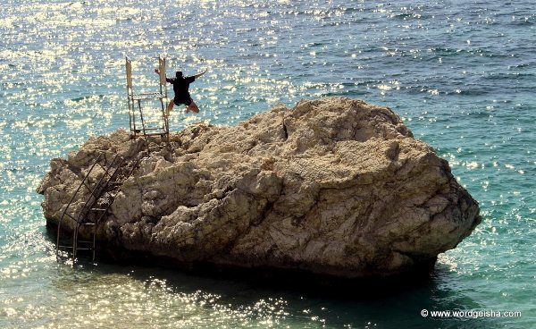 Jumping off rock into the sea.