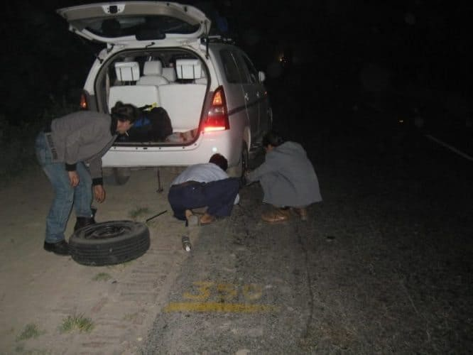 Changing a tire in the dark of night along the road.
