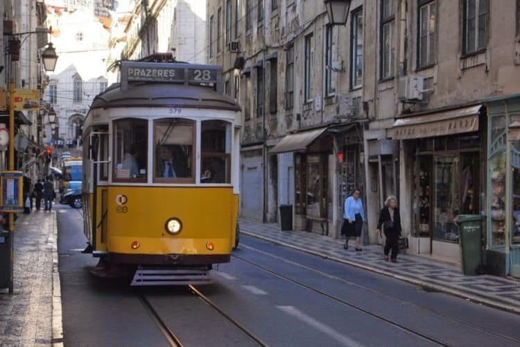 A yellow trolley chugs up a narrow Lisbon street.