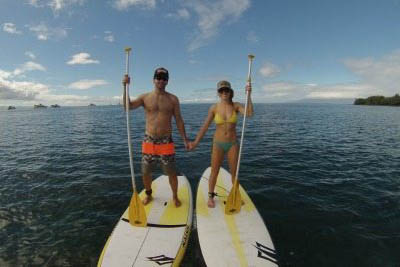 A couple holds hands while stand up paddle boarding. Maui Stand Up Paddle Boarding photos.