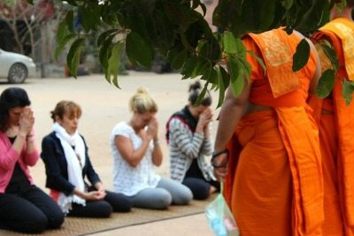 Participants kneel before monks in Cambodia.