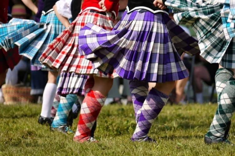 A Highland Dance costume consists of: tartan sock and kilt, velvet jacket with a lace insert, or a sleeveless velvet vest worn over a white blouse.
