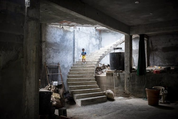 A boy descends a staircase inside of an unfinished church
