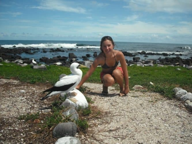 Ekaterina Golovina kneeling next to a bird, one of the four bird species that live on the island.