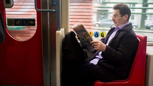 Man reading the newspaper on the train in Vienna. Andrew Castillo Photos.