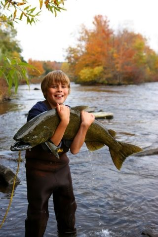 Thousand Islands has a dedicated fishing community -- a young boy holding a large salmon on the Salmon River in Pulaski in Oswego County! Oswego County Dept. of Tourism Photos.